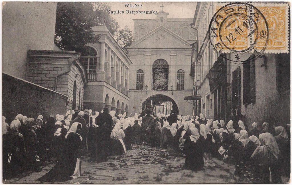 Kaart met een afbeelding van de Poort van het Morgenrood met de kapel. Op de kaart de Poolse aanduidingen, 'Wilno' en 'Kaplica Ostrobramska'. De kaart is aan de beeldzijde gefrankeerd met 2 kopeken: het drukwerktarief. Het stempel ВИЛЪНА [WILNA] heeft als datum 12-11-1912 en is een gewoon dubbelringsstempel
